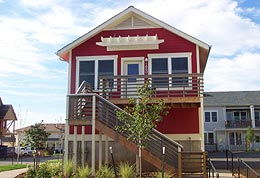 Holiday Neighborhood home: red with white trim and raised deck.