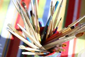 Paintbrushes against a colorful blanket table top at Ben's Bells studio.