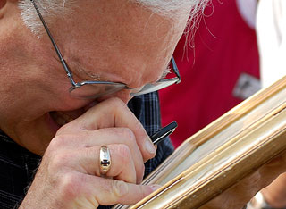 A closer look: a man investigates a frame for auction.