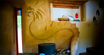 Cobb dragon sculpted into the wall of a cobb home at the Emerald Earth community.