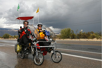 Ryan Mlynarczyk and Mandy Creighton of Within Reach as they pedal down a rainy Tucson, Ariz. street.