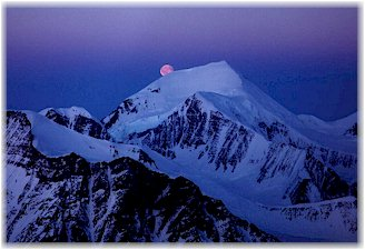 Moonrise over snowy mountain peak.