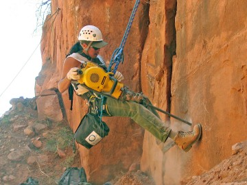Trail crew member drills into wall
