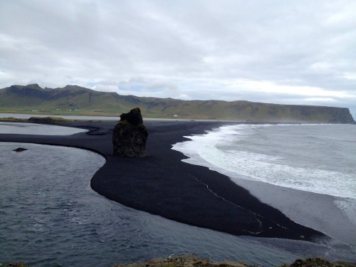 black sand beach reaching into the sea