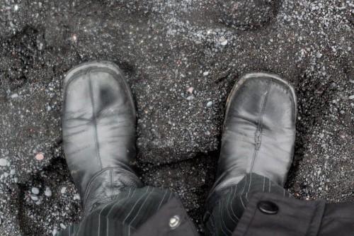 black boots, black sand