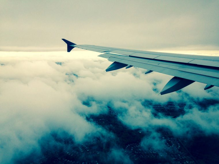 Airplane wing with clouds below