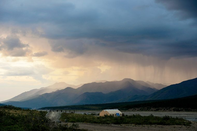 Visitor center tent and dramatic landscape with rain