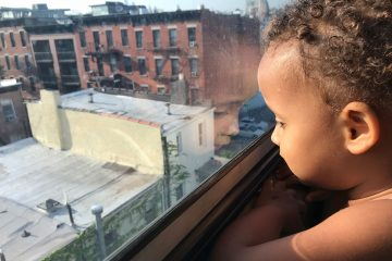 Child looking out window in Brooklyn